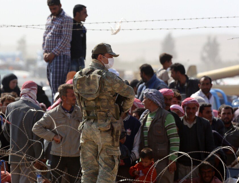 A Turkish soldier stands as Syrians from the town of Kobani wait to enter Turkey at the Yumurtalik border crossing Oct. 2.