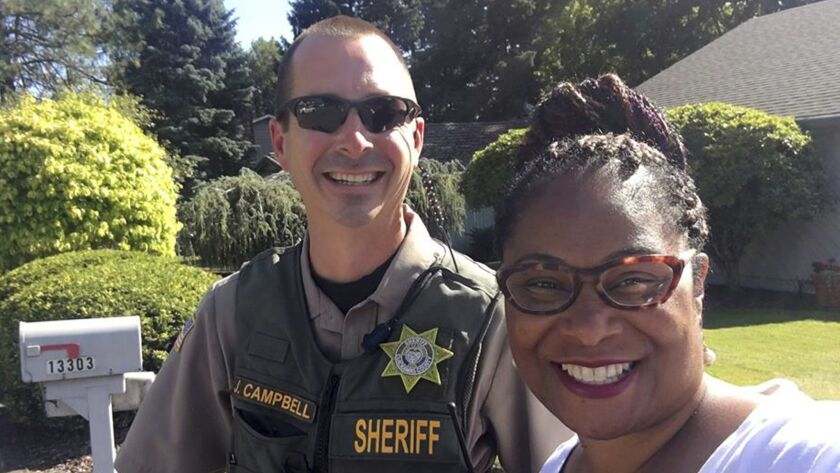 Oregon state Rep. Janelle Bynum, poses with a Clackamas County Sheriff's officer after he stopped her in Clackamas, Ore. on Tuesday.