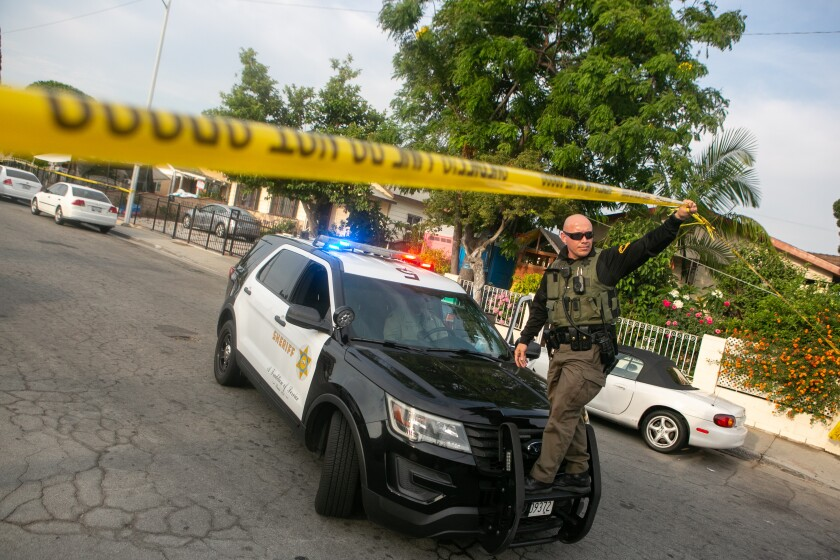 A police officer holds up some yellow police tape while standing on the bumper of a police vehicle in a residential street