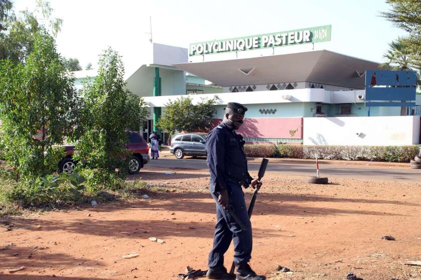 A police officer stands outside the quarantined Pasteur Clinic in Mali's capital, Bamako, on Nov. 12, 2014.