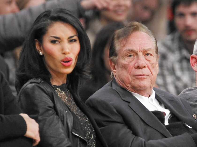 Donald Sterling and V. Stiviano watch the Clippers play. Sterling, then the team's owner, was fined $2.5 million by the NBA in April. A new state law bars sports team owners from writing off league penalties on their taxes.