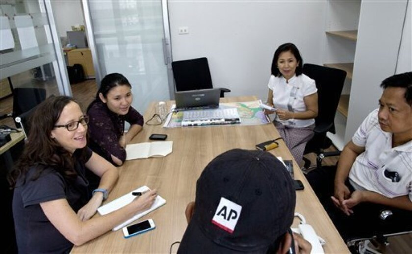 The Associated Press journalists, clockwise from left, Erika Kinetz, Yadana Htun, Aye Aye Win, Khin Maung Win and Zin Chit Aung attend a meeting in AP's new bureau in Yangon, Myanmar, Monday, April 1, 2013. The Associated Press has become the first international news agency to open a bureau in Myanmar since a reformist government took power two years ago and began relaxing restrictions on the media for the first time in decades. (AP Photo/Gemunu Amarasinghe)