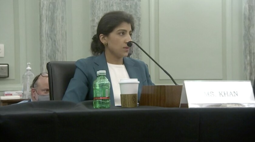 Lina Khan sits at a table, speaking into a microphone.