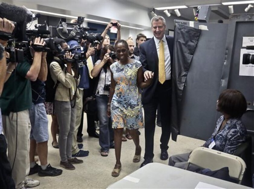 Mayoral candidate Bill de Blasio and his wife, Chirlane McCray, arrive to cast their primary votes, Tuesday, Sept. 10, 2013, at the Park Slope Public Library in the Brooklyn borough of New York. New Yorkers head to the polls Tuesday in a primary election that begins the process of replacing Michael Bloomberg, the billionaire mayor who has defined their city for 12 years. (AP Photo/Bebeto Matthews)