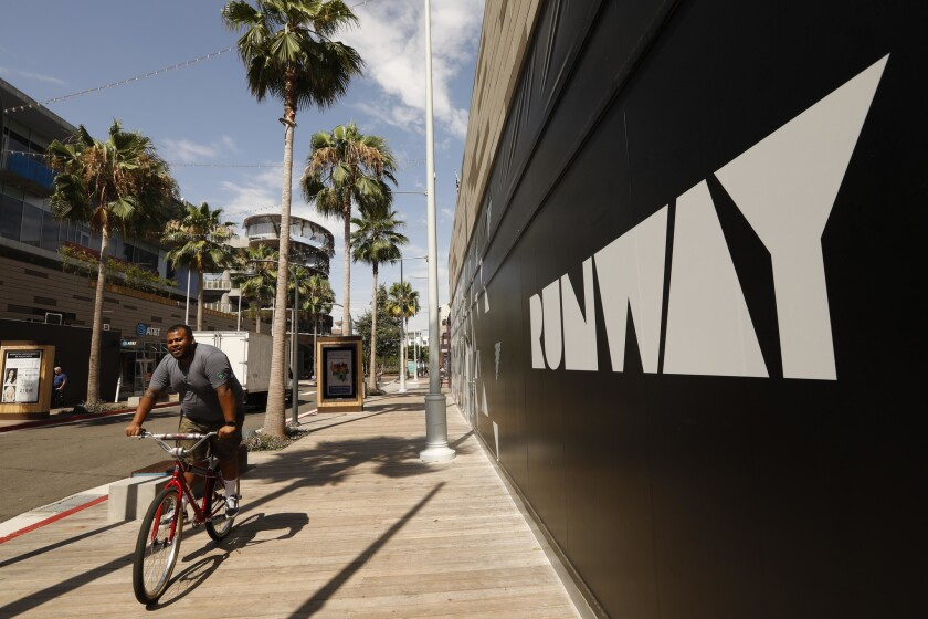 A bicyclist rides last month in the Runway shopping district in Playa Vista. Property manager DJM Capital Partners has decided to permanently close the middle section of Runway to auto traffic.
