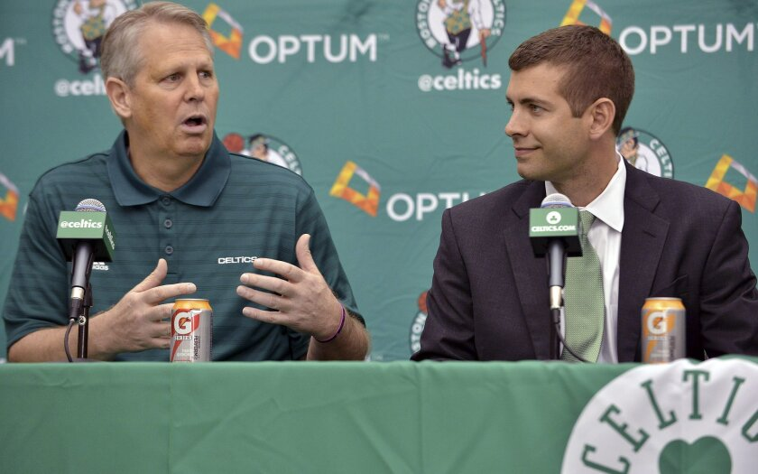 FILE - In this July 5, 2013, file photo, Boston Celtics general manager Danny Ainge, left, speaks alongside new head coach Brad Stevens, right, during an NBA basketball news conference in Waltham, Mass. Theoston Celtics have extended the contracts of  Stevens and Ainge, the team announced Wednesday