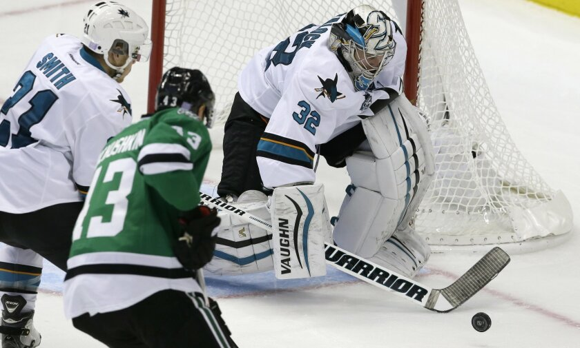 San Jose Sharks goalie Alex Stalock (32) deflects a shot in front of right wing Ben Smith (21) and Dallas Stars right wing Valeri Nichushkin (43) during the second period of an NHL hockey game Saturday, Oct. 31, 2015, in Dallas. (AP Photo/LM Otero)