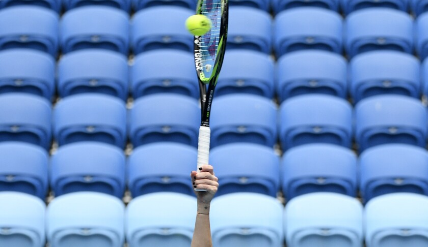 Marketa Vondrousova of the Czech Republic smashes the ball to Taiwan's Hsieh Su-Wei in front of rows of empty seats during their fourth round match at the Australian Open tennis championships in Melbourne, Australia, Sunday, Feb. 14, 2021. The Australian Open continues but without crowds after the Victoria state government imposed a five-day lockdown in response to a COVID-19 outbreak at a quarantine hotel. (AP Photo/Andy Brownbill)