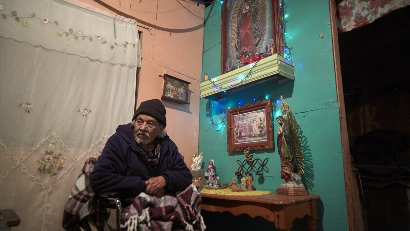 Jose Arias looks on from his home along the border in Tijuana, Mexico. According to the U.S. Border Patrol, Arias' shrine encroaches on U.S. soil, which posed a dilemma for the Trump administration as it pursued a replacement of 14 miles of barrier stretching east from the Pacific Ocean: Should the shrine be saved or destroyed?