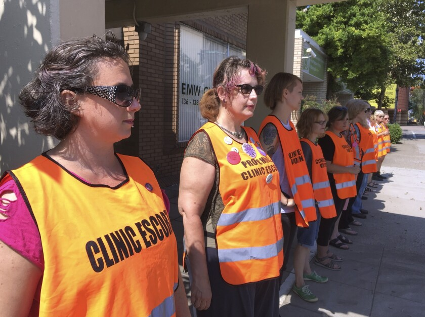 FILE - In this July 17, 2017 file photo, escort volunteers line up outside the EMW Women's Surgical Center in Louisville, Ky., the state's only abortion clinic. Kentucky's Attorney General Daniel Cameron, an anti-abortion supporter, said Friday, March 27, 2020, that abortions should cease as part of the governor's order halting elective medical procedures in the state due to the coronavirus pandemic. (AP Photo/Dylan Lovan, File)