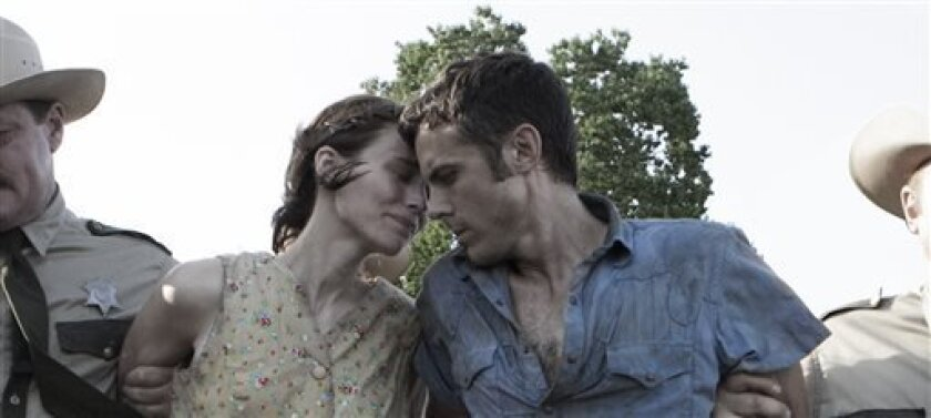 """This film image released by IFC Films shows Rooney Mara, left, and Casey Affleck in a scene from """"Ain't Them Bodies Saints."""" (AP Photo/IFC Films)"""