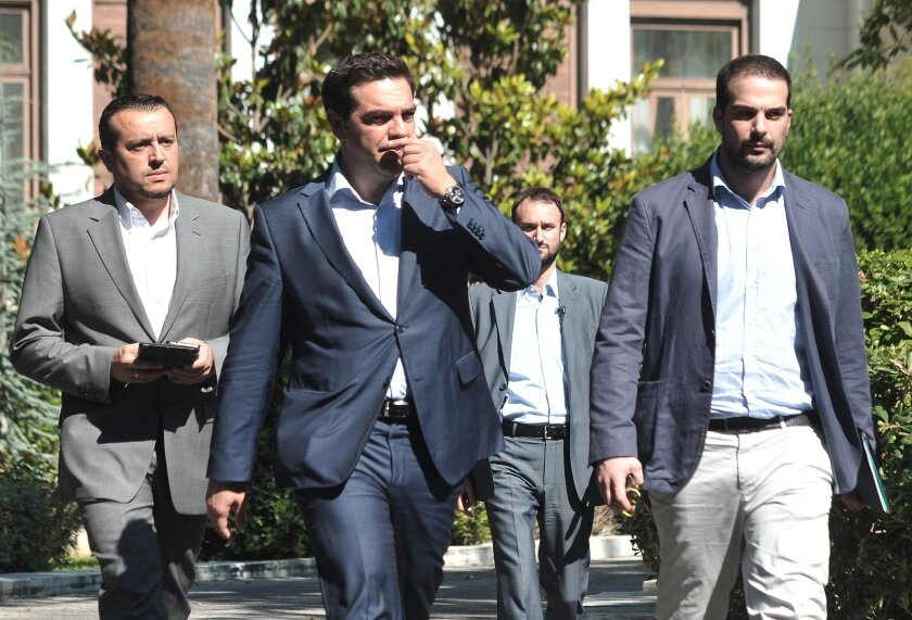 Greece's Prime Minister Alexis Tsipras, center, leaves after a meeting with Greek political party leaders at the Presidential Palace as Minister of State Nikos Pappas, left, and Government spokesman Gabriel Sakellaridis, right, follow him in Athens, Monday, July 6, 2015. Greece and its membership i