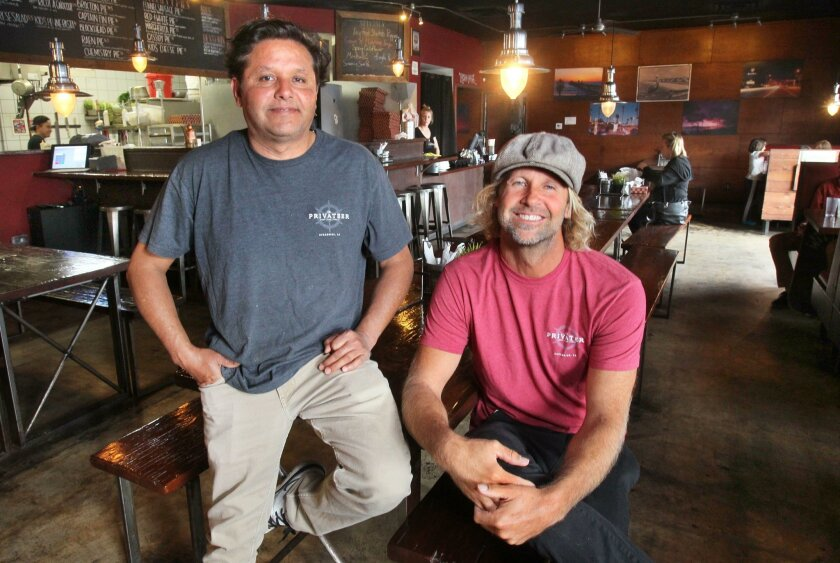 Privateer Coal Fire pizza owners Hector Reyna (left) and Charlie Anderson relax at their South Oceanside restaurant on Tuesday.