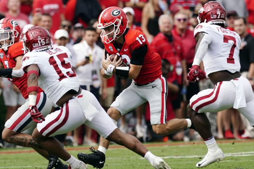 Georgia quarterback Stetson Bennett (13) tries to run past Arkansas defensive backs Simeon Blair (15) and Joe Foucha (7) during the first half of an NCAA college football game Saturday, Oct. 2, 2021, in Athens, Ga. (AP Photo/John Bazemore)