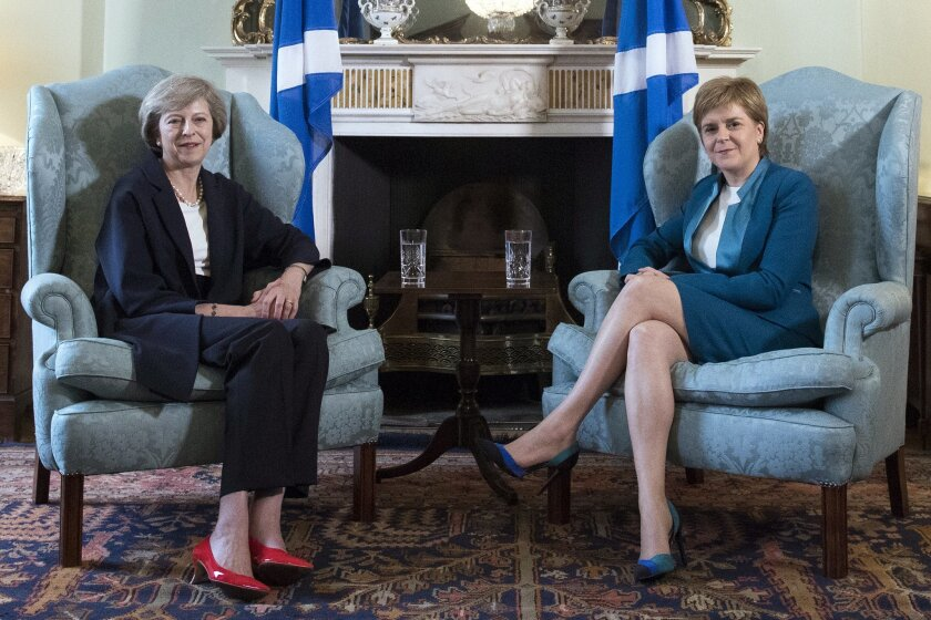 "Britain's new Prime Minister Theresa May, left, meets with First Minister of Scotland, Nicola Sturgeon at Bute House in Edinburgh, Scotland, Friday July 15, 2016, with Scottish saltire flags behind. Prior to the meeting, May said ""This visit to Scotland is my first as prime minister and I'm coming here to show my commitment to preserving this special union that has endured for centuries."" (Pool via AP)"
