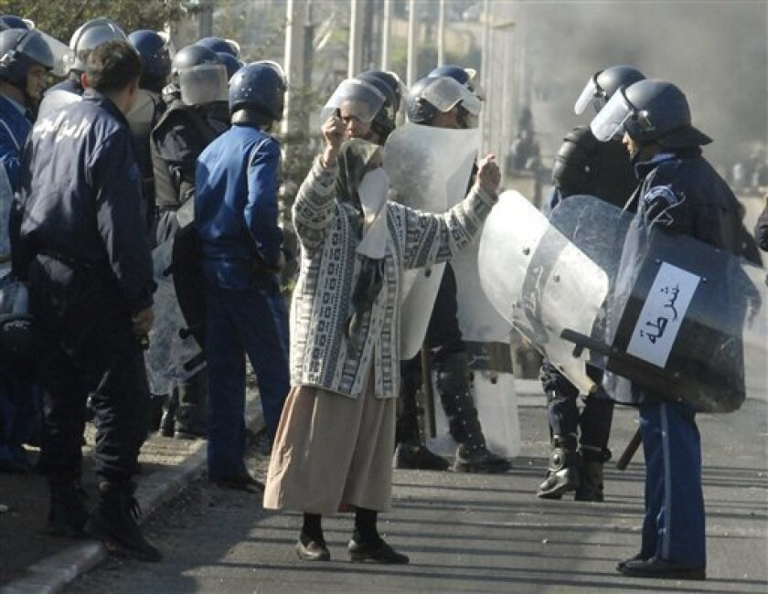 A woman reacts at police officers during clashes in the El Harrache district of Algiers, Thursday Jan.6, 2011. The violence came after price hikes for milk, sugar and flour in recent days, and amid simmering frustration that Algeria's abundant gas-and-oil resources have not translated into broader prosperity. Rioting youths set buildings and tires ablaze and hurled stones at police in the Algerian capital over rising food prices and chronic unemployment.(AP Photo)