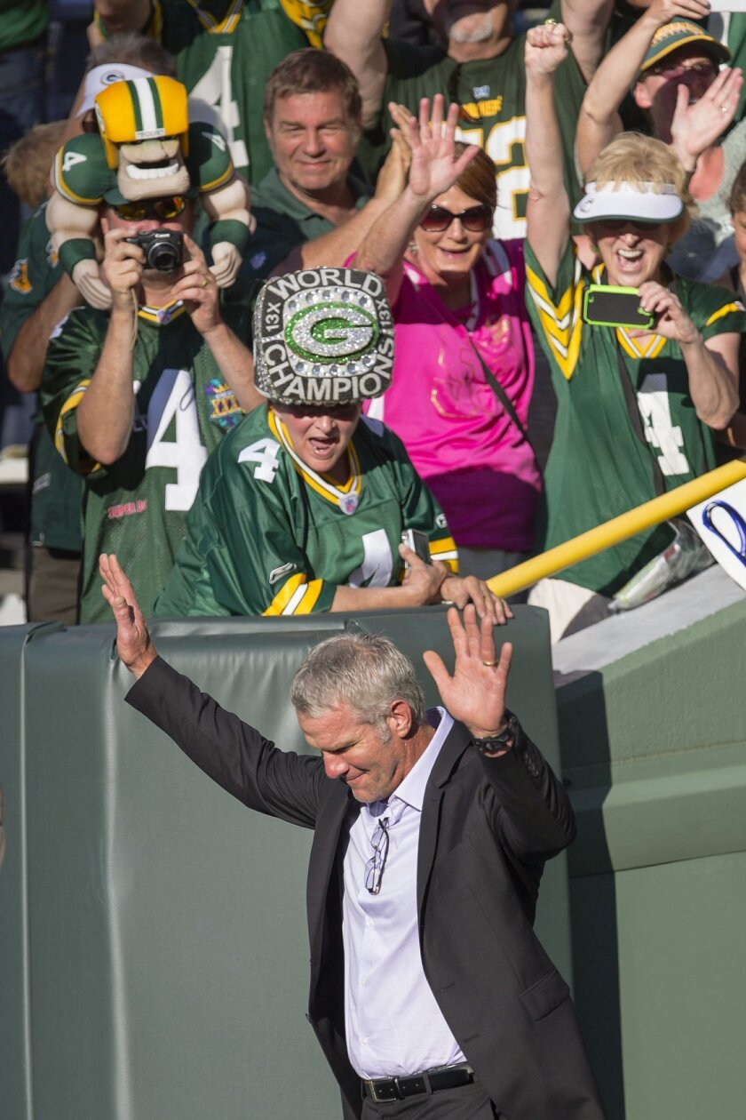Former Green Bay Packers quarterback Brett Favre waves to fans as he walks onto Lambeau Field prior to getting inducted in to the Packers Hall of Fame and having his No. 4 jersey retired, Saturday, July 18, 2015, in Green Bay, Wis. (AP Photo/Mike Roemer)
