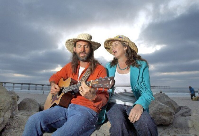 Street musicians Blair Schultze (left) and his wife, Kymythy, are fixtures near the Ocean Beach pier at sunset. (K.C. Alfred / Union-Tribune)