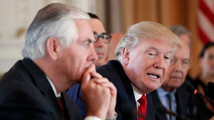 In this April 7, 2017, photo, President Donald Trump, joined by Secretary of State Rex Tillerson, le