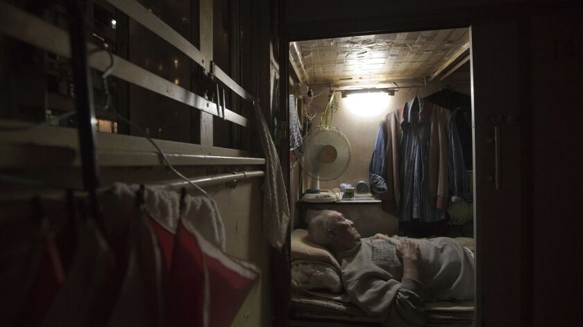 In this March 2017 photo, Tse Chu, a retired waiter, sleeps in his subdivided flat in Hong Kong. In wealthy Hong Kong, there's a dark side to a housing boom, with hundreds of thousands of people forced to live in partitioned shoebox apartments and other inadequate housing.