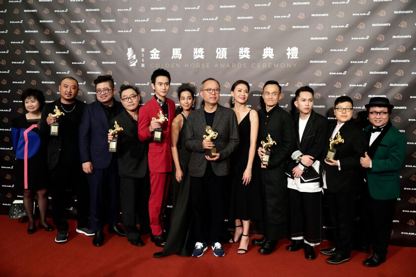 "Taiwanese film director Chung Mong-hong, center, and the cast of his movie ""A Sun"" pose for photographs after winning the Best Narrative Feature award at the 56th Golden Horse Awards ceremony in Taipei, Taiwan, on Nov. 23, 2019. The film awards established in 1962 are presented to filmmakers working in Chinese-language cinema."