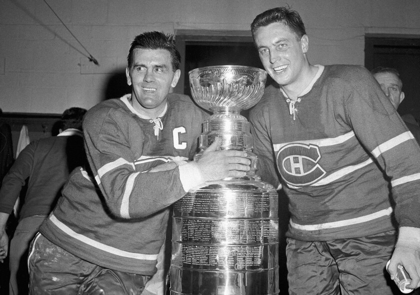 Maurice Richard, left, and Jean Beliveau stand on either side of the Stanley Cup after the Montreal Canadiens' victory over the Boston Bruins in 1958.
