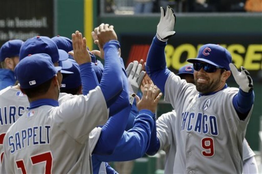 Chicago Cubs right fielder David DeJesus (9) celebrates with teammates after being introduced before a season opening baseball game against the Pittsburgh Pirates in Pittsburgh Monday, April 1, 2013. (AP Photo/Gene J. Puskar)