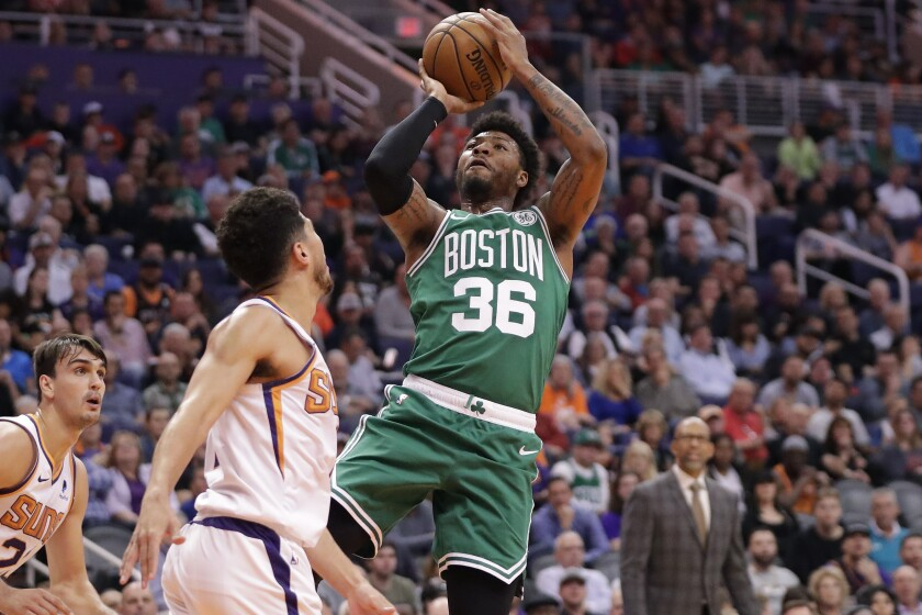 Boston Celtics guard Marcus Smart (36) shoots over Phoenix Suns guard Devin Booker during the first half of an NBA basketball game, Monday, Nov. 18, 2019, in Phoenix. (AP Photo/Matt York)
