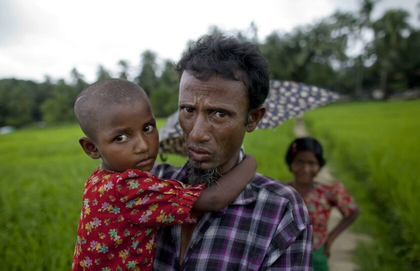 In this Sept. 17, 2013 photo, an ethnic Rohingya man, who was displaced following 2012 sectarian violence, walks carrying his daughter at Nga Chaung refugee Camp in Pauktaw, Rakhine state, Myanmar. Authorities sealed off villages for months in Myanmar's only Muslim-majority region and in some cases beat and arrested people who refused to register with immigration officials, residents and activists say, in what may be the most aggressive effort yet to compel Rohingya to identify themselves as illegal migrants from neighboring Bangladesh. (AP Photo/Gemunu Amarasinghe)