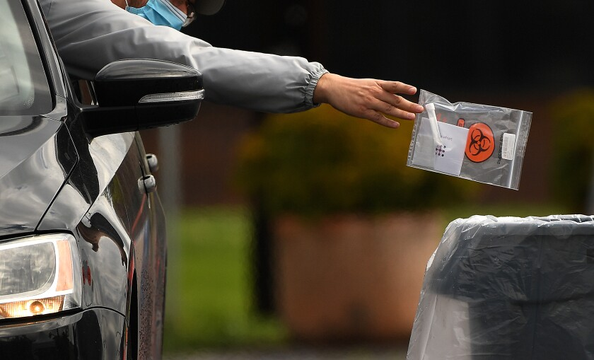 A driver leans out of their window with arm outstretched to drop a bagged coronavirus test specimen into a receptacle