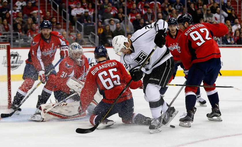 Kings' Trevor Lewis goes after the puck while surrounded by Washington Capitals players, including goalie Philipp Grubauer (31), Andre Burakovsky and Evgeny Kuznetsov.