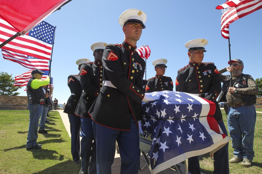 Marines with the United States Marines Honor Guard carry the casket of Marine Staff Sgt. Wesley Lee Kroenung Jr., a combat photographer who died in the World War II battle of Tarawa in 1943, as members of the Patriot Guard Riders hold American flags at Miramar National Cemetery on Wednesday, August 14, 2019 in San Diego, California.