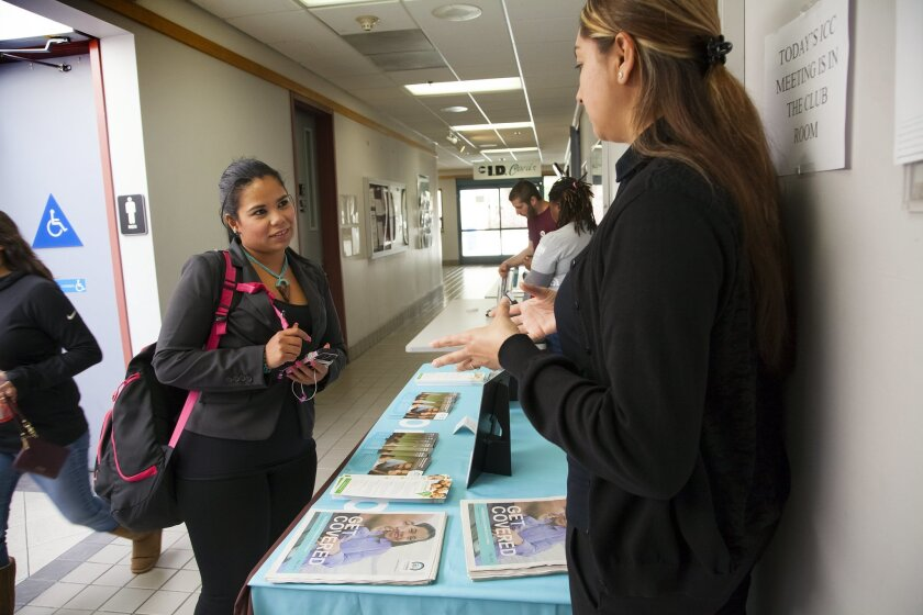 Full time student from MiraCosta College, Juliana Rico (left) stopped by to speak with Jessica Garcia about health coverage.  Rico became frustrated after spending almost an hour going through the online sign up process only to find that in the end the system crashed. and all her information was