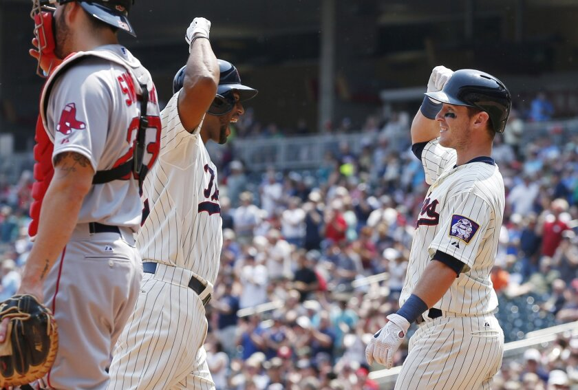 Minnesota Twins' Aaron Hicks, left, and Chris Herrmann celebrate Hicks' two-run home run off Boston Red Sox' pitcher Rick Porcello in the fourth inning of a baseball game, Wednesday May 27, 2015, in Minneapolis. (AP Photo/Jim Mone)