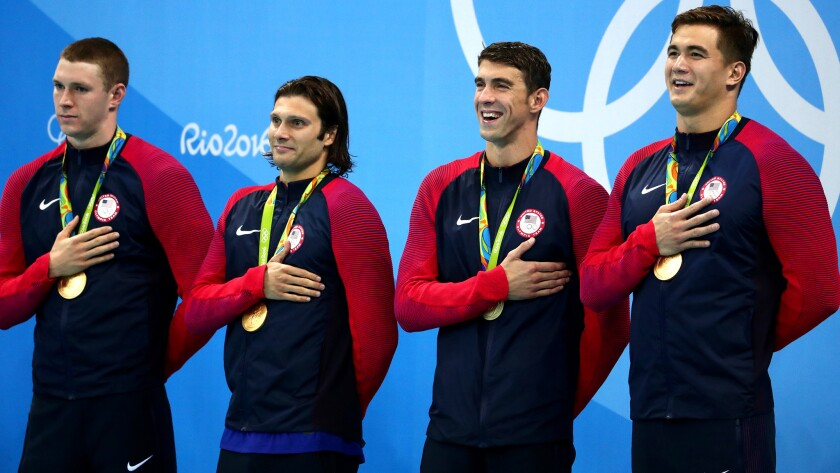 The U.S. men's 400-meter medley relay team -- (from left) Ryan Murphy, Cody Miller, Michael Phelps, Nathan Adrian -- listen to the national anthem after winning gold on Saturday night.
