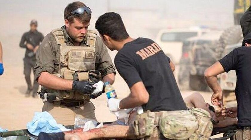 Derek Coleman (with the sunglasses) treats a wounded Kurdish soldier in Iraq.