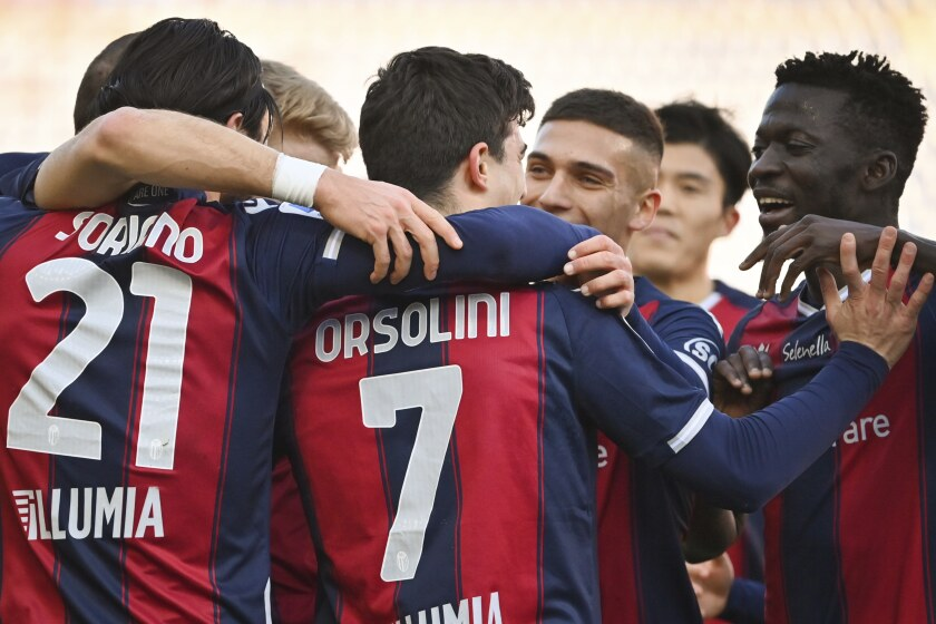 Bologna's Riccardo Orsolini celebrates with teammates after scoring his side's first goal on a penalty kick during the Serie A soccer match between Bologna and Verona at the Renato Dall'Ara stadium, in Bologna, Italy, Saturday, Jan. 16, 2021. (Massimo Paolone/LaPresse via AP)