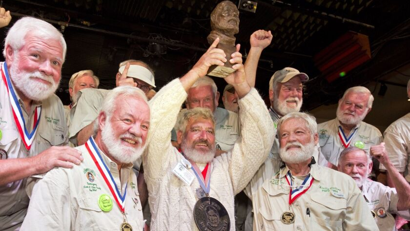 "Dave Hemingway, center, hoists his trophy after winning the 2016 Ernest ""Papa"" Hemingway Look-Alike"