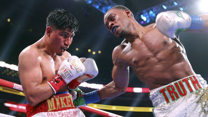Mikey Garcia, left, takes a blow to the body from Errol Spence Jr. during the ninth round of the IBF welterweight championship bout on March 16, 2019, in Arlington, Texas.