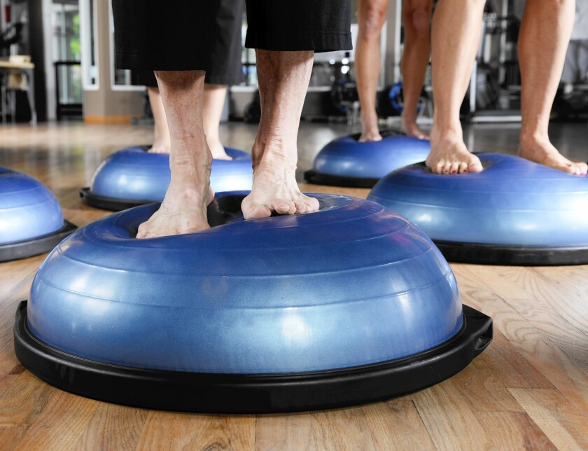 A Pilates class uses BOSU balls for balance exercises, which become even more important as we get older.