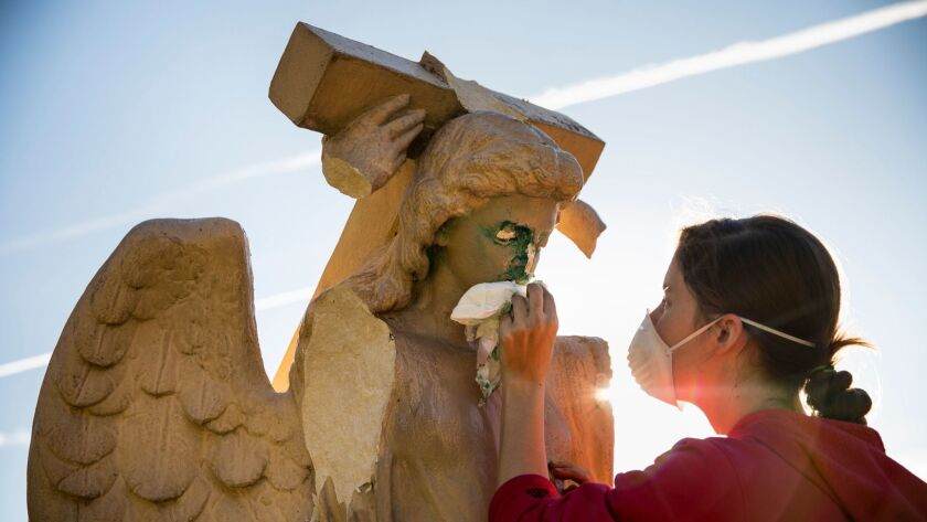 Evelyn Askew, 19, cleans an angel statue that was damaged and spray-painted with graffiti in front of Church of the Angels in Pasadena.