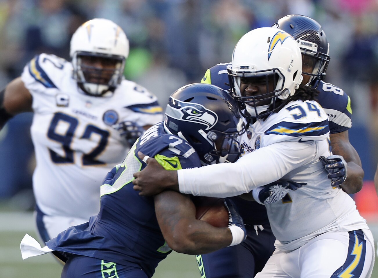 Chargers defensive end Melvin Ingram III wraps up Seattle Seahawks running back Mike Davis in the third quarter Sunday at Century Link Field in Seattle.