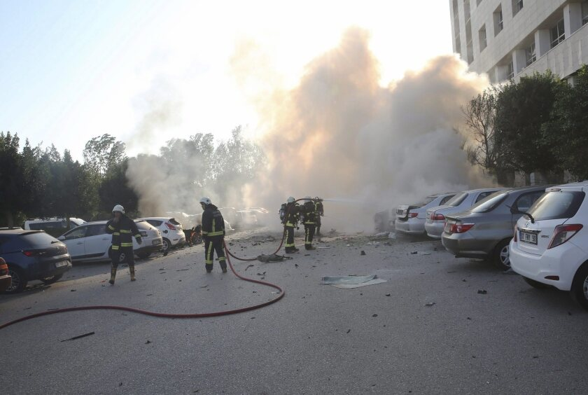 Firefighters try to extinguish a fire after an explosion in the parking area of the Antalya Trade and Industry Chamber building in Antalya, Turkey, on Oct. 25, 2016.