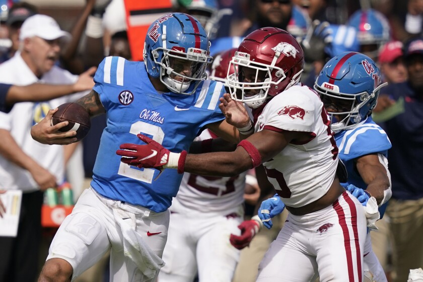 Mississippi quarterback Matt Corral, left, pushes off an Arkansas defender during the second half of an NCAA college football game, Saturday, Oct. 9, 2021, in Oxford, Miss. Mississippi won 52-51.(AP Photo/Rogelio V. Solis)