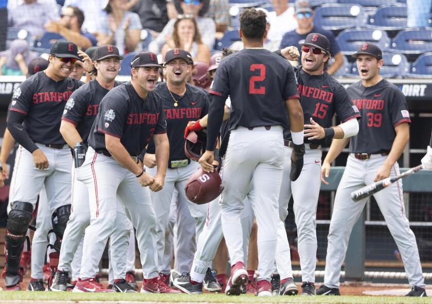 Stanford players celebrate as Tommy Troy, obscured behind Drew Bowser. (2), returns to the dugout after hitting a two-run home run against Arizona in the third inning during a baseball game in the College World Series Monday, June 21, 2021, at TD Ameritrade Park in Omaha, Neb. (AP Photo/Rebecca S. Gratz)