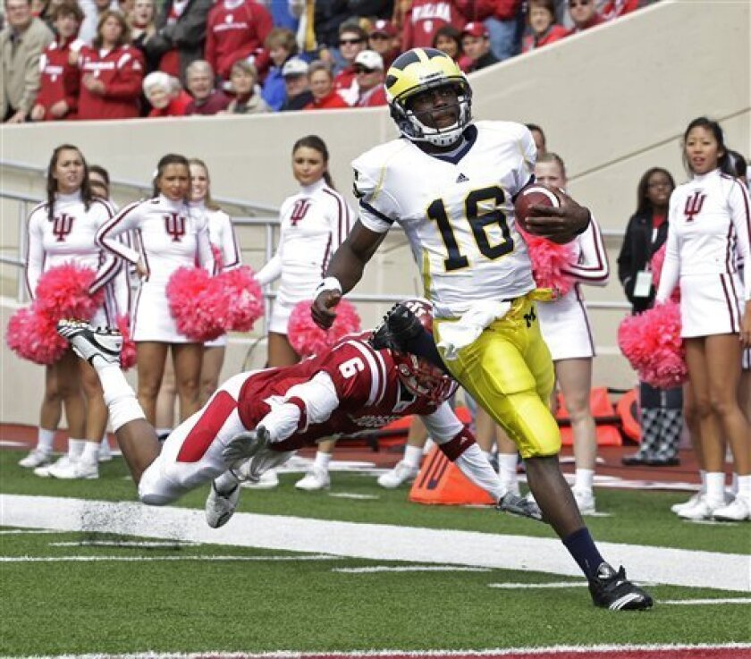 Michigan quarterback Denard Robinson (16) approaches the end zone on a 72-yard touchdown run while being chased by Indiana cornerback Richard Council (6) during the first quarter of an NCAA college football game in Bloomington, Ind., Saturday, Oct. 2, 2010. (AP Photo/Darron Cummings)