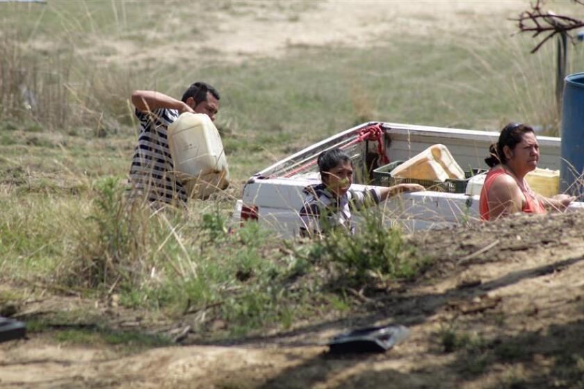 Fotografía del 22 de mayo de 2017 del varias personas rellenando contenedores con gasolina durante la ordeña clandestina de un ducto de la empresa Petróleos Méxicanos (Pemex). EFE/Archivo