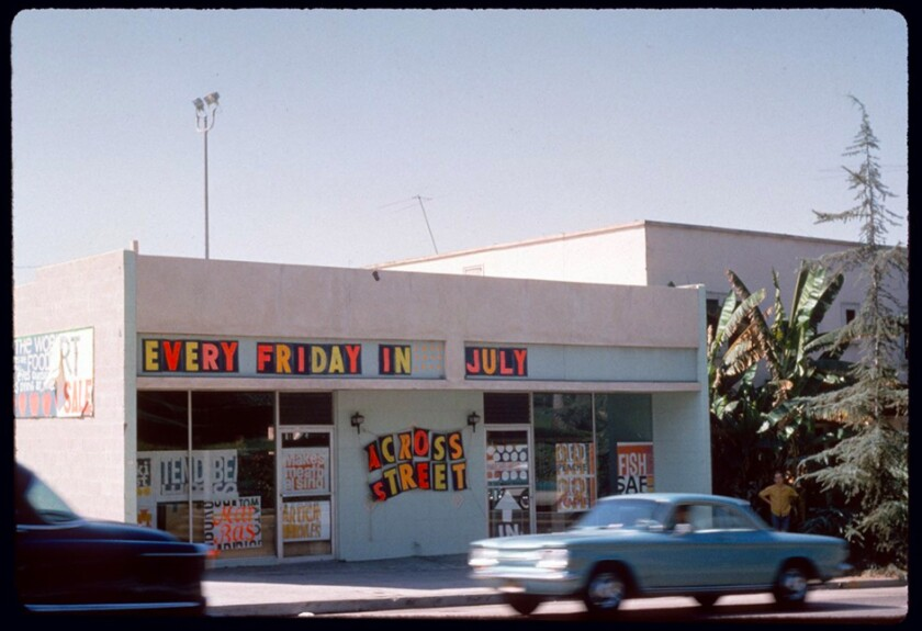 """A 1960s image shows a car driving past a storefront covered in bright prints and a sign that reads """"Every Friday in July"""""""