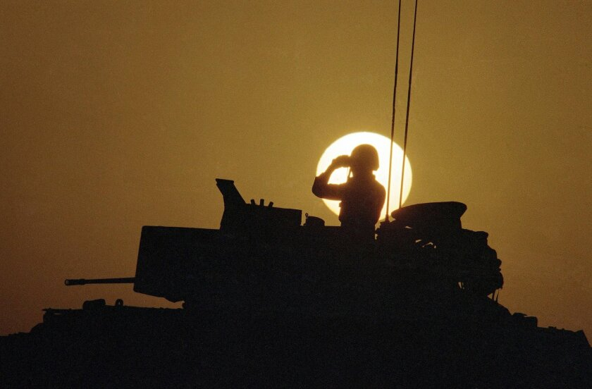 A Bradley Fighting Vehicle commander from the 24th Infantry Division keeps watch as the sun sets on his base in the Saudi Arabian desert in 1990.