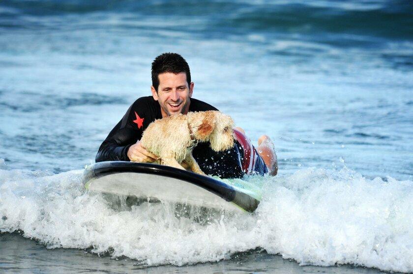 Mike Samer and his dog Lambeau enjoy paddleboarding at La Jolla Shores.